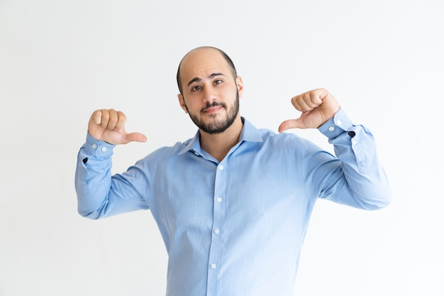 Hombre joven confiado que señala en sí mismo y que mira la cámara