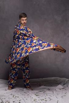 Hombre joven confiado que sopla su cortina floral contra la pared gris