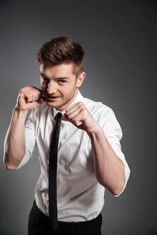 Hombre joven confidente en boxeo de ropa formal