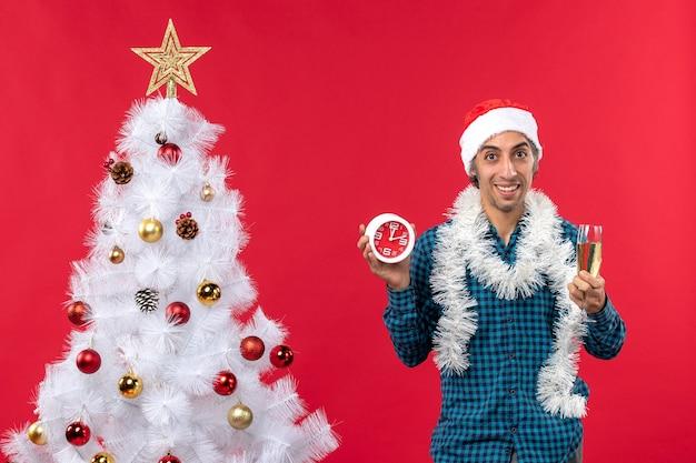 Hombre joven confidente con sombrero de santa claus y sosteniendo una copa de vino y reloj de pie cerca del árbol de navidad