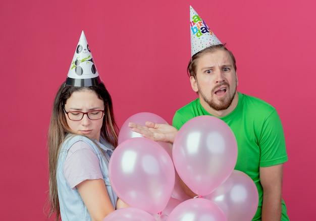 Hombre joven confundido con sombrero de fiesta apunta a la niña ofendida de pie con globos de helio aislados en la pared rosa