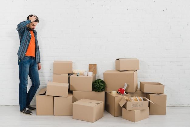 Hombre joven confuso que mira pilas de cajas de cartón contra la pared de ladrillo blanca
