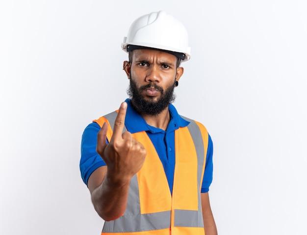 Hombre joven constructor afroamericano disgustado en uniforme con casco de seguridad apuntando hacia arriba aislado en la pared blanca con espacio de copia