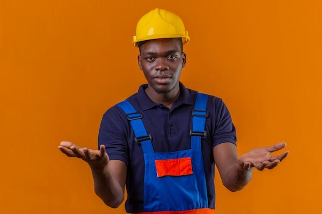 Hombre joven constructor afroamericano vestido con uniforme de construcción y casco de seguridad haciendo gesto confuso con las manos y expresión como pregunta en naranja aislada