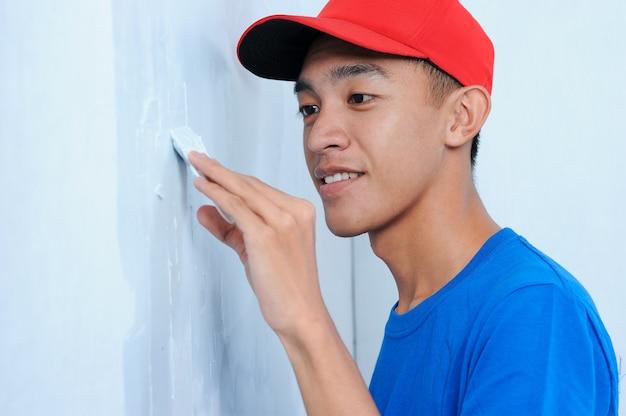Hombre joven constructor asiático aplicando yeso en la pared blanca. enlucido de pared a pared de acabado.