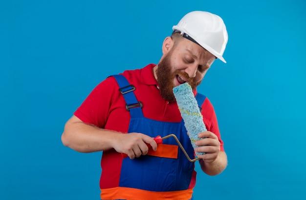 Hombre joven constructor barbudo en uniforme de construcción y casco de seguridad con rodillo de pintura usando como micrófono cantando, divirtiéndose en el trabajo