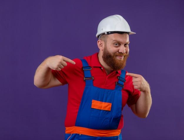 Hombre joven constructor barbudo en uniforme de construcción y casco de seguridad sonriendo confiado apuntando a sí mismo con los dedos índices sobre fondo púrpura