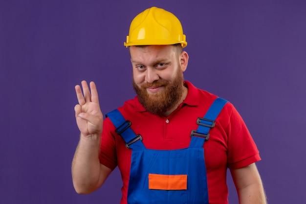 Hombre joven constructor barbudo en uniforme de construcción y casco de seguridad sonriendo mostrando y apuntando hacia arriba con los dedos número tres sobre fondo púrpura