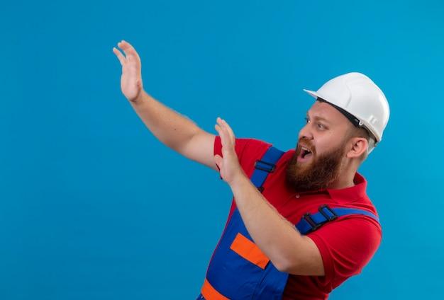 Hombre joven constructor barbudo en uniforme de construcción y casco de seguridad tomados de la mano haciendo gesto de defensa mirando asustado gritando