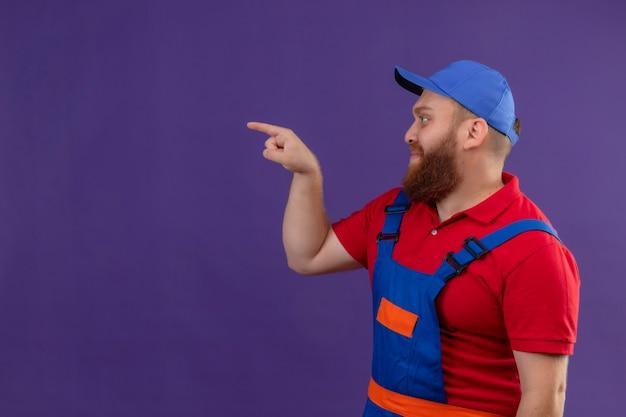 Hombre joven constructor barbudo en uniforme de construcción y gorra mirando a un lado apuntando con el dedo índice a algo sobre fondo púrpura