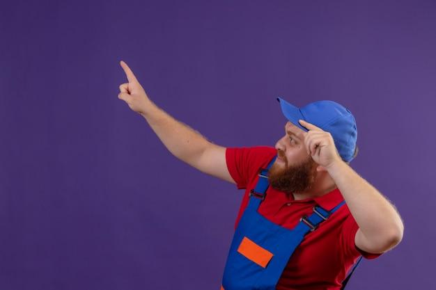Hombre joven constructor barbudo en uniforme de construcción y gorra mirando a un lado preocupado apuntando con el dedo índice a algo sobre fondo púrpura
