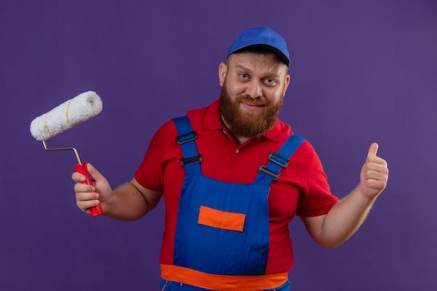 Hombre joven constructor barbudo en uniforme de construcción y tapa con rodillo de pintura sonriendo mostrando los pulgares para arriba sobre fondo púrpura