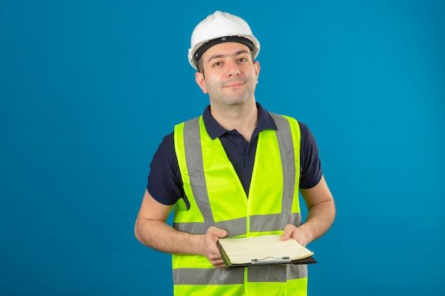Hombre joven constructor con casco blanco y un chaleco amarillo, sosteniendo portapapeles en manos de pie en azul aislado
