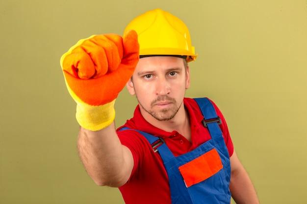 Hombre joven constructor en guantes de uniforme de construcción y casco de seguridad golpeando puerta o ventana ficticia sobre pared verde aislado