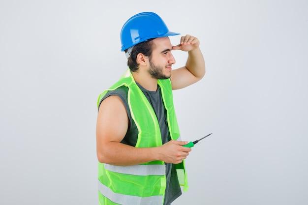 Hombre joven constructor manteniendo el destornillador mientras sostiene la mano en la cabeza para ver claramente en uniforme y lucir feliz. vista frontal.
