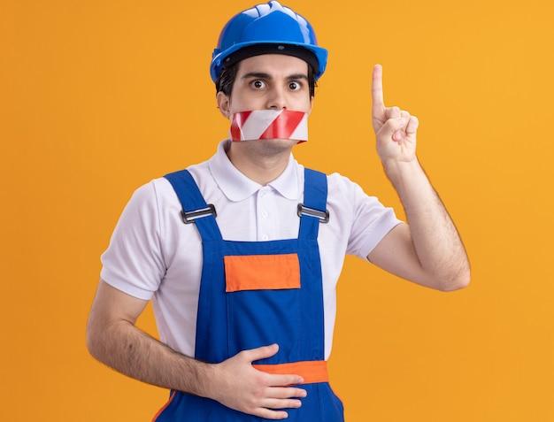 Hombre joven constructor en uniforme de construcción y casco de seguridad con cinta envuelta alrededor de la boca mirando al frente preocupado apuntando con el dedo índice sobre la pared naranja