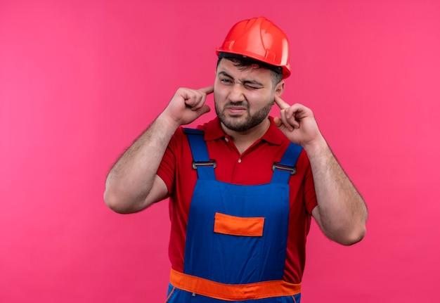 Hombre joven constructor en uniforme de construcción y casco de seguridad cubriendo las orejas con los dedos con expresión molesta por el ruido del sonido fuerte