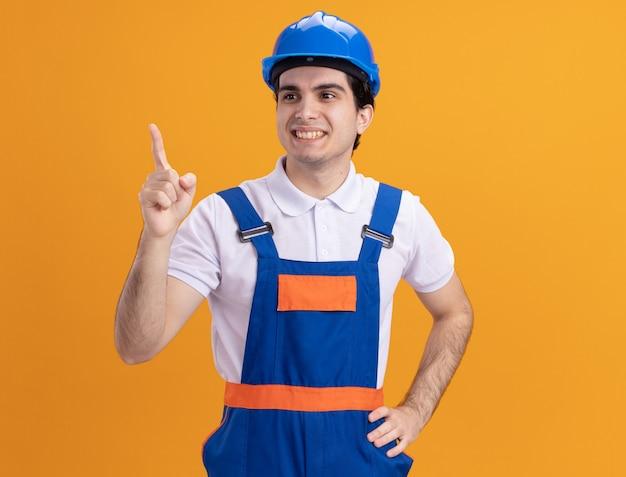 Hombre joven constructor en uniforme de construcción y casco de seguridad mirando a un lado sonriendo confiado apuntando con el dedo índice a algo parado sobre la pared naranja