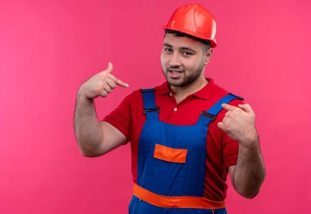Hombre joven constructor en uniforme de construcción y casco de seguridad mirando sintiéndose pround apuntando con los dedos índices a sí mismo