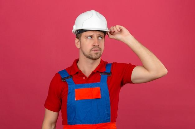 Hombre joven constructor en uniforme de construcción y casco de seguridad pensando con la mano en la cabeza mirada confundida teniendo dudas sobre la pared rosa aislada