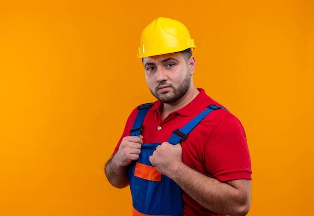 Hombre joven constructor en uniforme de construcción y casco de seguridad tomados de la mano en el pecho mirando a cámara ar con expresión seria y confiada