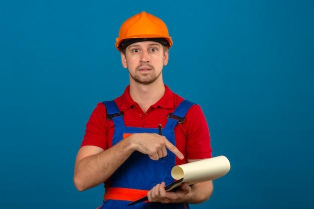 Hombre joven constructor en uniforme de construcción y seguridad helmetyoung hombre constructor en uniforme de construcción y casco de seguridad con cara sorprendida apuntando al portapapeles en manos ove