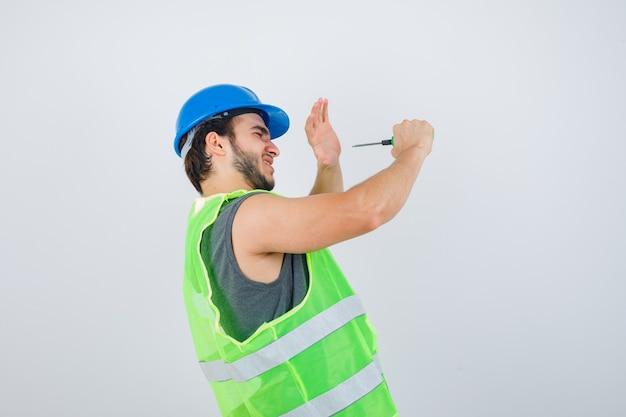 Hombre joven constructor en uniforme fingiendo golpearse con un destornillador y mirando loco, vista frontal.