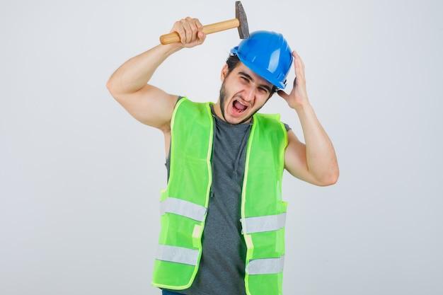 Hombre joven constructor en uniforme golpeando la cabeza con un martillo y mirando divertido, vista frontal.