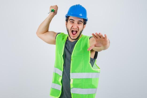 Hombre joven constructor en uniforme golpeando con destornillador y mirando loco, vista frontal.