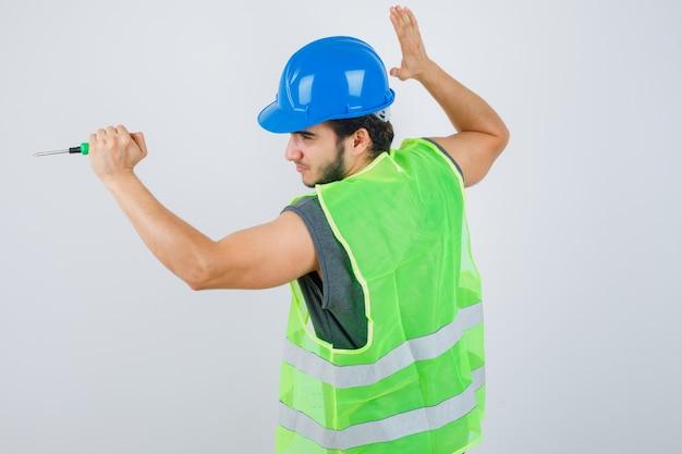 Hombre joven constructor en uniforme levantando la mano para golpear con un destornillador y mirando loco, vista frontal.
