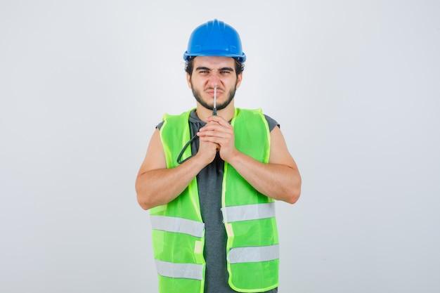 Hombre joven constructor en uniforme presionando la nariz con un destornillador y mirando divertido, vista frontal.