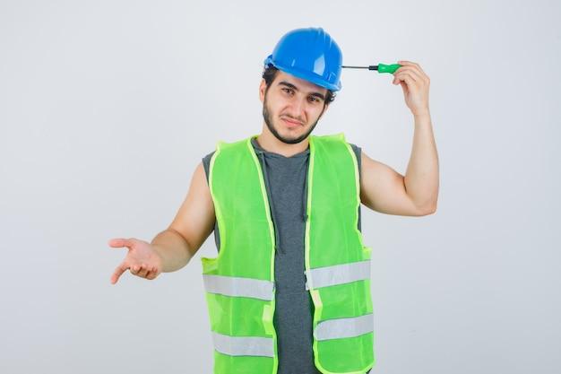 Hombre joven constructor en uniforme sosteniendo la punta del destornillador en la cabeza y mirando vacilante, vista frontal.