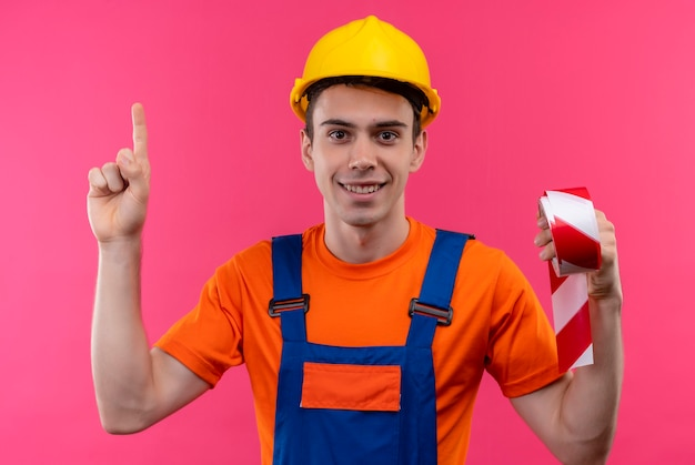 Hombre joven constructor vestido con uniforme de construcción y casco de seguridad apunta con el pulgar hacia arriba y sostiene cinta de señalización roja-blanca