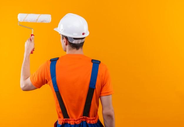 Hombre joven constructor vestido con uniforme de construcción y casco de seguridad blanco pinta la pared con cepillo de rodillo