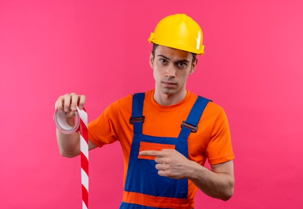 Hombre joven constructor vestido con uniforme de construcción y puntos de casco de seguridad en una cinta de señalización roja-blanca