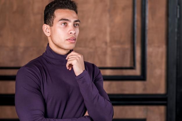 Hombre joven contemplado de pie contra la pared