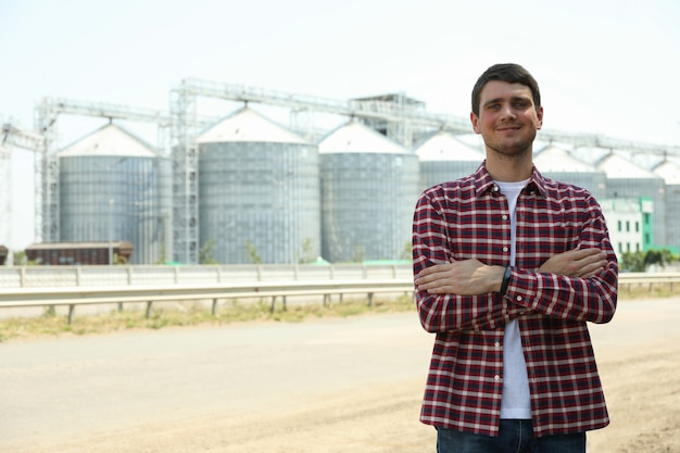 Hombre joven contra silos de grano. negocio agrícola