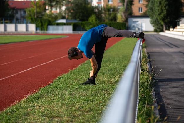 Hombre joven corredor lleva auriculares haciendo estiramientos en la pista de atletismo. espacio vacio