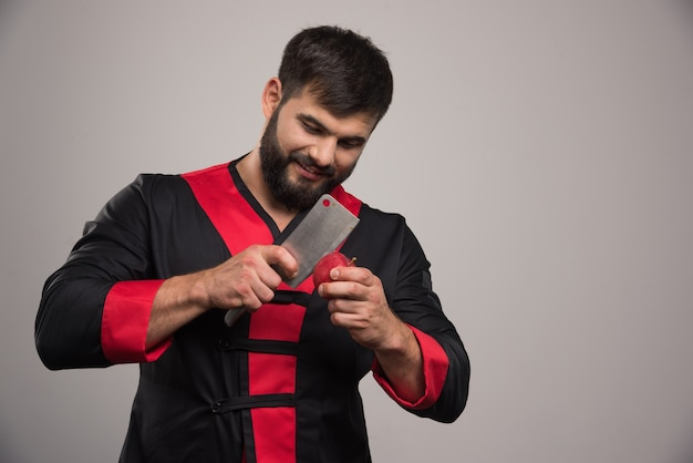 Hombre joven cortando con cuchillo manzana roja.