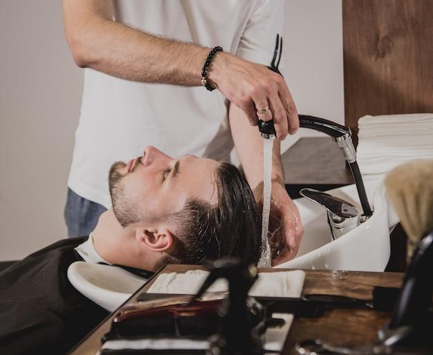 Hombre joven con corte de pelo de moda en peluquería. barbero lava la cabeza del cliente.