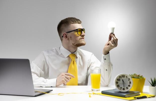 Hombre joven creativo que mira la bombilla ardiente en mano. idea de negocio de inicio