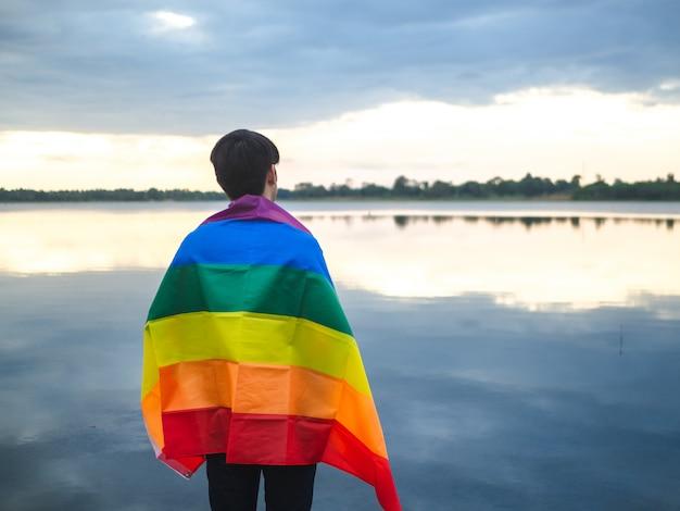 Hombre joven cubierto por una bandera del arco iris al lado del lago en fondo del cielo de la puesta del sol.