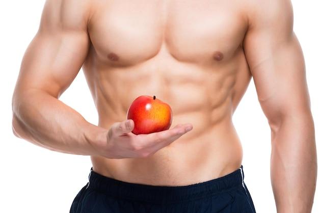 Hombre joven con cuerpo perfecto sosteniendo manzana roja en su mano