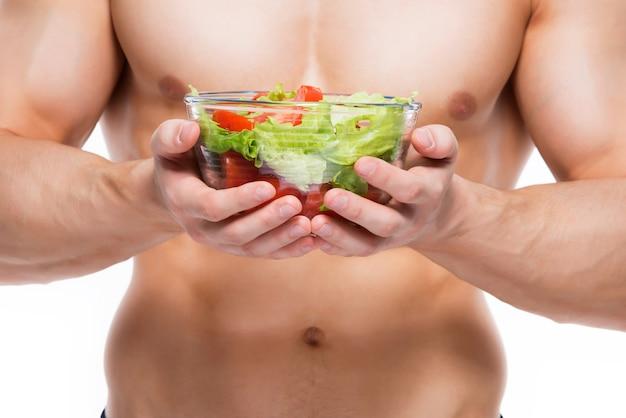 Hombre joven con cuerpo perfecto tiene ensalada - aislada en la pared blanca.