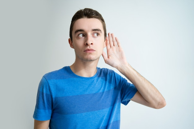 Hombre joven curioso que lleva a cabo la mano cerca de la oreja