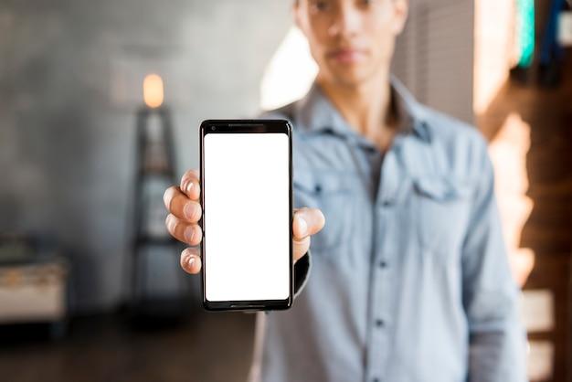 Hombre joven defocused que muestra el teléfono móvil de la pantalla blanca