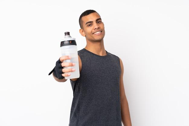 Hombre joven del deporte afroamericano sobre la pared blanca aislada con la botella de agua deportiva