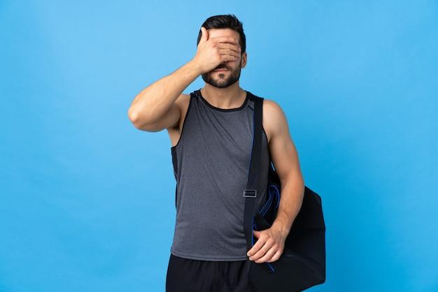 Hombre joven deporte con bolsa de deporte en la pared azul que cubre los ojos con las manos. no quiero ver algo