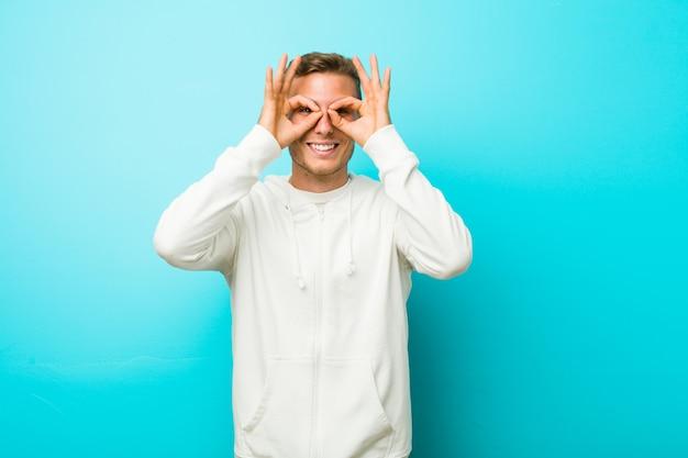Hombre joven deporte caucásico que muestra bien firmar sobre los ojos