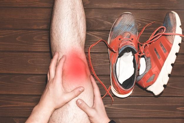 Hombre joven deporte con fuertes piernas atléticas sosteniendo la rodilla con las manos en el dolor